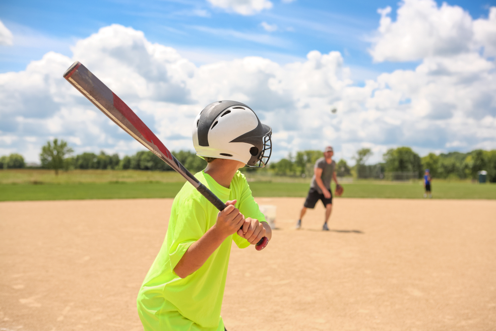 Baseball practice, coach pitching to batter - Image